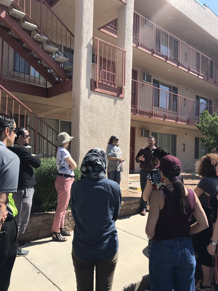 A group of people stand outside a three-story apartment complex.