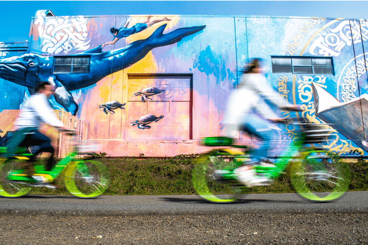 Two people riding green bikes in front of a large colorful mural on the side of a building.