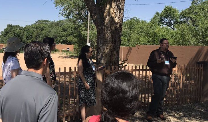 People stand and talk under a tree by an empty plot of land.