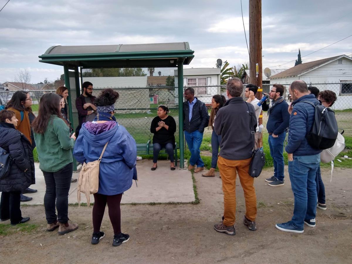 Isabel speaking to a group in front of a neighborhood bus stop.